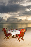 Candlelight dinner at the beach. Table with two chairs arranged at the beach for a candlelight dinner Royalty Free Stock Images