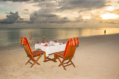 Candlelight dinner at the beach. Table with two chairs arranged at the beach for a candlelight dinner Royalty Free Stock Image