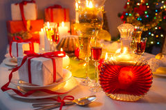 Candlelight and gifts all around the Christmas table Royalty Free Stock Images