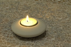 Candlelight on glitter background. Candlelight in white candlestick holder on glitter background Stock Photo