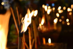 Candlelight. Group of burning candles on black background Stock Photos