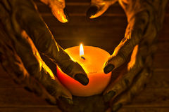 Candlelight illuminating the werewolf hands. The two-toned candlelight illuminating the werewolf hands for Halloween concept Stock Image