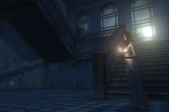 Candlelight and moonlight. Young woman in nightgown with candlestick at the foot or an ornate staircase an a rundown building Stock Photography