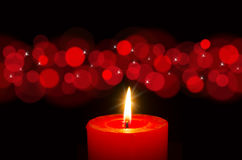 Candlelight - Red burning candle Stock Photos