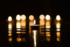 Candlelight with reflections. Single candle and reflection of multiple candles in the background Stock Image