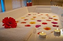 Candlelit bath in health spa with flowers stock photos
