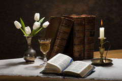 Candlelit Bible. Still life image of an open bible on a table along with a candle and candle holder, a vase of white tulips, a glass of wine, old books, a pocket royalty free stock images
