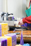 Candlemaker at work in a chandler. Straightening decorative candles that have been removed from their moulds,cropped view of the hands with colorful ornamental Stock Images