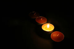 Candles 01. Four small orange candels in the dark stock images