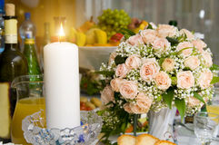 Candles. The Candles and bouquet roses on a banquet table, beautifully  brightly burn Royalty Free Stock Photo