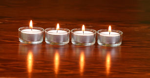 Candles. Burning candles on the dark wooden surface Royalty Free Stock Image