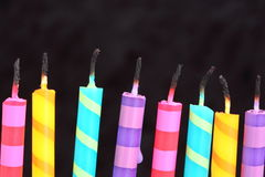 Candles. Several colored striped candles that have been lit Stock Image