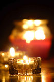 Candles. Several candles glowing with dark background and reflections on wood Royalty Free Stock Photo