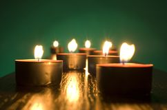 Candles. Group of small candles on green background Stock Photos