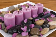 Candles. Aromatic candles and rose petals on pebbles Royalty Free Stock Photos