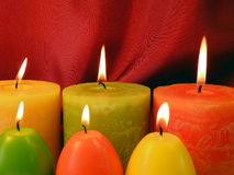 Candles. Colorful candles on red satin background Royalty Free Stock Images