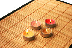 Candles. Colorful candles on bamboo over white Royalty Free Stock Images