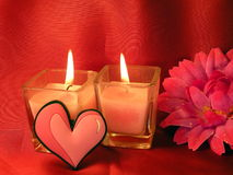 Candles. Two candles, heart and flower on red satin Royalty Free Stock Image