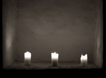 Candles. Three white candles in a black room royalty free stock images