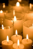 Candles. With some in glasses. Focused on the candle near the glasses Royalty Free Stock Images