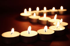 Candles. Close-up of an arrangement of lit candles on a red background Stock Images