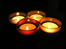 Candles. Four lit candles in the dark royalty free stock photos