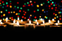 Candles against the backdrop of colored lights Royalty Free Stock Images