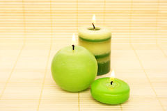Candles on bamboo. Three green candles on bamboo background Stock Photos