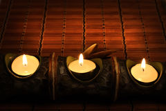 Candles on bamboo rug Royalty Free Stock Photos