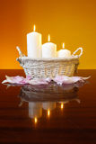 Candles in basket on orange background Stock Images