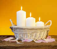Candles in basket, orange background Stock Photo
