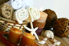 Candles and bath towels. Bathroom scene of bath towels in baskets, lit candles, seashells and woven decorations Stock Photo