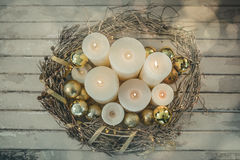 Candles and bauble ball in nest basket on wooden plank Stock Photography