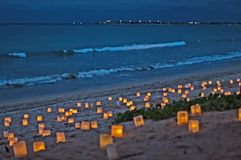 Candles on Beach at Dusk. Photo taken in Bali, Indonesian. Dozens of candles in palm leaf enclosures can be seen. The ocean waves are gently lapping on the beach stock photos