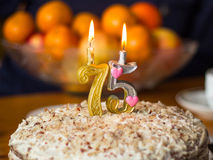 Candles on the birthday cake. Two candles on the birthday cake on the background of the vase with oranges Royalty Free Stock Photo
