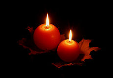 Candles on black. A pair of burning candles decorated by maple leaves, on a black background Royalty Free Stock Photos