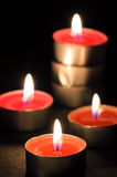 Candles on a black background. Four burning candles on a black background Royalty Free Stock Image