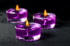 Candles on a black background with water drops Stock Photos