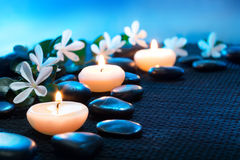 Candles and black stones on black mat. Blue light royalty free stock image