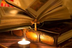 Candles, books and bible on a dark background. The light from the burning candle. Prayer stock image