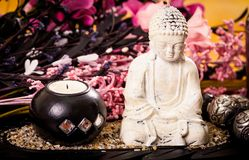 Candles and buddha statue with flowers spa concept Stock Image