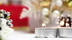 Candles burn and croak in the wind in the New Year`s installation in white and red tones stock video footage