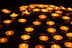 Candles burn in dark Catholic cathedral Royalty Free Stock Images