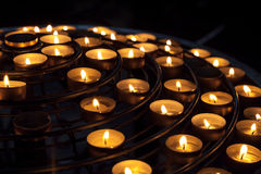 Candles burn in dark interior of Catholic cathedral Royalty Free Stock Images