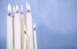 Candles burning against blue background Royalty Free Stock Photo