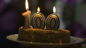 Candles burning on 100 anniversary cake, number of subscribers, company success. Stock footage stock footage