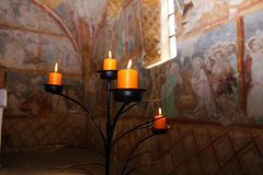 Candles burning on black candleholder inside ancient fresco wall. S Royalty Free Stock Photos