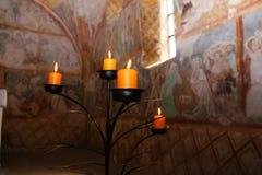Candles burning on black candleholder inside ancient fresco wall Royalty Free Stock Photos