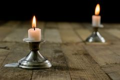 Candles burning in candlesticks on a wooden table. Silver candle stock photos