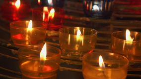 Candles burning in catholic church. Festive glow in cathedral. Holy place illuminated by flames stock video footage